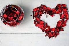心脏和一个碗玫瑰花瓣 免版税库存照片