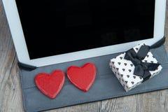 心脏和一件礼物与一种数字式片剂 免版税库存图片