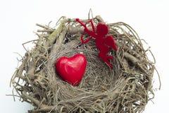 心脏和丘比特形象被安置入一只木鸟筑巢 库存图片