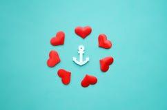 心脏和船锚在蓝色背景 免版税库存照片