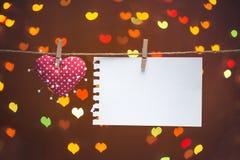 心脏和针与笔记关于晒衣绳 背景蓝色框概念概念性日礼品重点查出珠宝信函生活纤管红色仍然被塑造的华伦泰 库存图片
