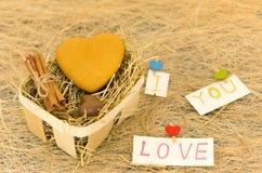 心脏和题字我爱你 曲奇饼和巧克力以心脏的形式 与干草的篮子 免版税库存图片