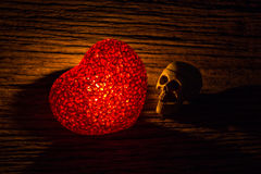 心脏和头骨在黑暗 免版税库存图片