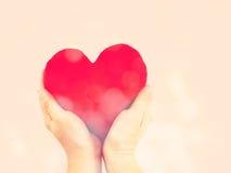 心脏在手上有葡萄酒过滤器颜色背景 免版税图库摄影
