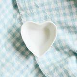 心脏在浅兰的检查样式布料背景的形状盘 库存照片
