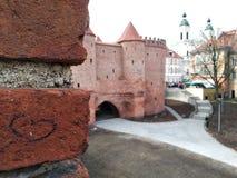 心脏在砖墙上,爱老城市 城堡在现代大厦附近 历史中心在镇 对的接触 免版税库存照片
