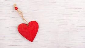 心脏垂饰由木头制成 红色重点 免版税库存照片