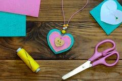 心脏垂饰项链 毛毡心脏下垂项链,剪刀,螺纹,毛毡在一张木桌上覆盖 情人节首饰工艺 免版税库存图片
