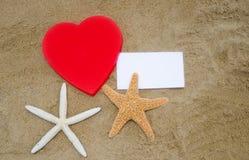 心脏形状、海星和纸在海滩 库存图片