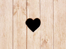 心脏形状在木墙壁、洗手间、wc门或者窗口上切开了 免版税库存图片