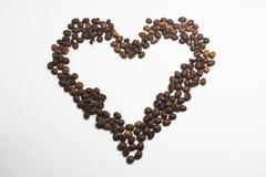心脏形状在白色背景隔绝的咖啡豆 重点查出的形状蕃茄白色 仍然锂 免版税库存照片