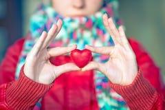 心脏形状爱标志在有面孔的妇女手上在背景 图库摄影