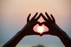 心脏形状用人工和海日落做 免版税库存照片