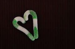 心脏形状由两绿色和白色条纹棒棒糖做成 库存图片