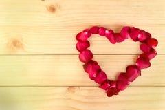 心脏形状由玫瑰花瓣做成在木背景, Valentin 库存照片