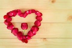心脏形状由玫瑰花瓣做成在木背景, Valentin 免版税库存照片