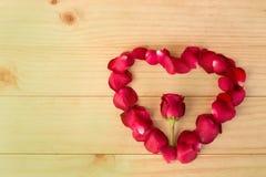 心脏形状由玫瑰花瓣做成在木背景, Valentin 免版税库存图片