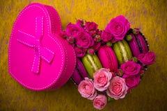 心脏形状箱子有莓果桃红色春天颜色充满爱的蛋白杏仁饼干背景 免版税库存照片