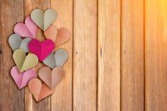 心脏形状纸用与木背景机智的淡色切开了 库存照片