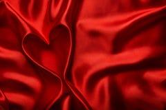 心脏形状,红色丝绸布料背景,织品折叠作为摘要 免版税库存照片