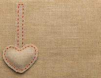 心脏形状麻袋布缝合的对象 被修理的粗麻布背景 免版税库存照片