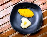 心脏标志甜黏米饭和芒果在黑盘 免版税库存照片
