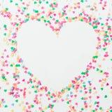 心脏标志由五颜六色的明亮的五彩纸屑制成在白色背景 平的位置,顶视图拷贝空间 概念亲吻妇女的爱人 免版税库存图片