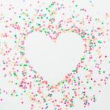 心脏标志由五颜六色的明亮的五彩纸屑制成在白色背景 平的位置,顶视图拷贝空间 概念亲吻妇女的爱人 图库摄影