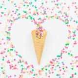 心脏标志由五颜六色的明亮的五彩纸屑和奶蛋烘饼锥体制成在白色背景 平的位置,顶视图拷贝空间 概念亲吻妇女的爱人 图库摄影