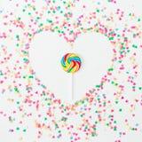 心脏标志由五颜六色的明亮的五彩纸屑和糖果制成在白色背景 平的位置,顶视图拷贝空间 概念亲吻妇女的爱人 库存照片