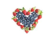 心脏标志由新鲜的蓝莓和草莓制成在白色 库存图片