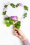 心脏标志由flovers和叶子制成在白色背景 免版税库存照片