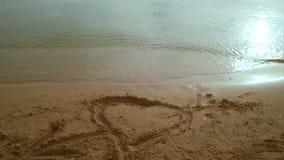 从心脏标志的摇摄在对海景视图的沙子 与心脏形状的海海滩 股票录像