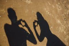 心脏海滩的simbols新婚佳偶剪影  免版税图库摄影