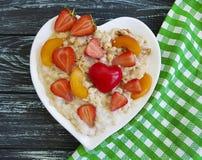 心脏燕麦粥粥,草莓,在木背景的杏子板材  免版税图库摄影
