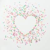 心脏爱标志由五颜六色的明亮的五彩纸屑制成在白色背景 平的位置,顶视图拷贝空间 库存图片