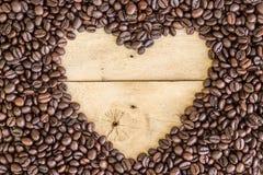 心脏爱空间在木头的咖啡豆 免版税库存照片