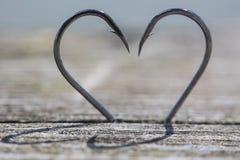 心脏由两个钓鱼钩制成 库存图片