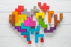心脏由五颜六色的木形状做成,顶视图,平的位置 免版税图库摄影