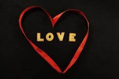 心脏由充满里面词爱的红色丝带制成 免版税库存图片