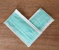 心脏由医疗防护蓝色和白色面具做成 免版税库存图片