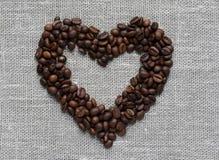 心脏由咖啡豆制成在一种亚麻制织品 免版税图库摄影