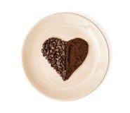 心脏由咖啡豆和碾碎的咖啡在板材, Valen制成 库存照片