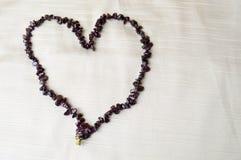 心脏由女性美丽的小珠,棕色黑暗的石头项链做成,琥珀色反对米黄织品背景  库存图片