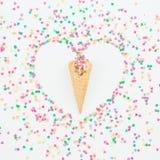 心脏由明亮的糖果五彩纸屑和奶蛋烘饼锥体制成在白色背景 平的位置,顶视图拷贝空间 概念亲吻妇女的爱人 免版税库存照片