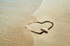 心脏由沙子制成在海滩 概念亲吻妇女的爱人 免版税库存图片