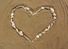 心脏由海制成轰击在沙子 免版税库存照片