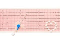 心脏由白色心脏形状片剂和蓝色塑料导尿管制成有开放针的在纸ECG结果 免版税图库摄影