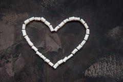 心脏由白色心脏蛋白软糖,爱的装饰制成 免版税库存照片