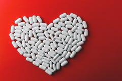 心脏由白色药片在红色背景,心脏病疗程做成 库存图片